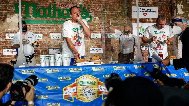 Competitive eater Joey Chestnut sets a new world record with 75 hot dogs to win the men's division of the Nathan's Famous July Fourth hot dog eating contest, Saturday, July 4, 2020, in the Brooklyn borough of New York. AP Photo/John Minchillo)