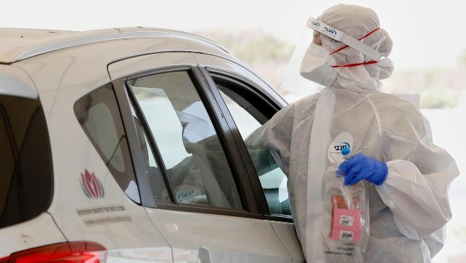 Israeli medical personnel take samples at a drive through COVID-19 testing facility in Ramat Hasharon in the suburbs of Tel Aviv, on July 6, 2020 during measures imposed by the Israeli authorities to curb the spread of the novel coronavirus. (Photo by JACK GUEZ / AFP)